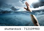 Small photo of Hand of person drowning in water