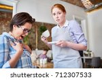 embarrassed waitress with cup... | Shutterstock . vector #712307533
