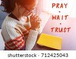 woman praying  pray wait trust | Shutterstock . vector #712425043