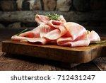 sliced ham on wooden background.... | Shutterstock . vector #712431247