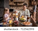 happy family having breakfast... | Shutterstock . vector #712562593