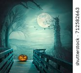 Small photo of Spooky, autumn forest with dead trees, old wooden bridge, pumpkin, bats and roots at full moon night. Halloween concept.
