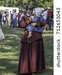 Small photo of WHEATON, ILLINOIS/USA - SEPTEMBER 10, 2017: A young woman in period dress holds a toddler close during a military ceremony (off camera) at a reenactment of the American Revolutionary War (1775-1783).