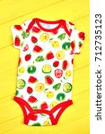 Small photo of Infants fruit print soft bodysuit. Baby cute cotton summer romper on yellow wooden background. Newborn kids high quality apparel.