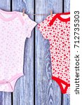 Small photo of Infant girls patterned clothes on rope. Baby girl summer printed rompers hanging and drying on clothesline, vintage wooden background.