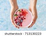 woman's hands holding a pink... | Shutterstock . vector #713130223