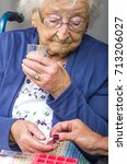 Small photo of Senior Citizen taking Pill. A senior citizen, in a wheelchair, being given her medication by a carer.