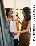Small photo of Fashion consultant giving dress to a woman in fitting room