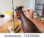Woman Gluing Tiny Shaped...