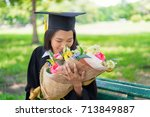 Small photo of Educational theme.Woman graduating and Beautiful bouquet of congratulations in an academic gown.