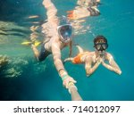 father and son  snorkel in... | Shutterstock . vector #714012097