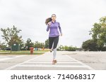 woman jogging and crossing the... | Shutterstock . vector #714068317