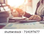 business woman using calculator ... | Shutterstock . vector #714197677