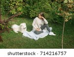 young woman resting with a dog... | Shutterstock . vector #714216757