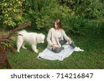 young woman resting with a dog... | Shutterstock . vector #714216847