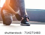 young woman tying her shoelaces ... | Shutterstock . vector #714271483