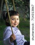Small photo of little girl swinging on a swing and smiling/little girl swinging on a swing in the garden