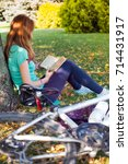 girl in the park sits under a... | Shutterstock . vector #714431917
