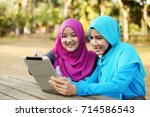 muslim lady working on smiling | Shutterstock . vector #714586543