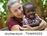 Small photo of Adoption symbol - Woman adopts a little African boy