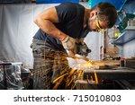 a young brunette man welder in... | Shutterstock . vector #715010803