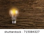 glowing light bulb on wood... | Shutterstock . vector #715084327