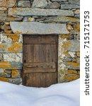 Small photo of Soana Valley, Piedmont, Italy - December 2016: Entrance door of stone hut blocked by snow.