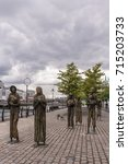 Small photo of Dublin, Ireland - August 7, 2017: Great Irish Famine bronze statue set on Custom House Quay along Liffey River in Docklands. All six figures, male and female, plus dog. Green trees and cloudscape.