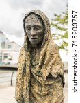 Small photo of Dublin, Ireland - August 7, 2017: Great Irish Famine bronze statue set on Custom House Quay along Liffey River in Docklands. One slender female figure. Green trees and gray sky.