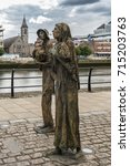 Small photo of Dublin, Ireland - August 7, 2017: Great Irish Famine bronze statue set on Custom House Quay along Liffey River in Docklands.. Two figures, male and female, out of six plus dog total.