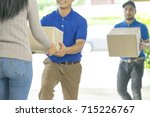two deliverymen holding boxes... | Shutterstock . vector #715226767