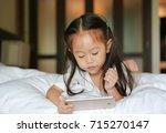 cute little girl looking mobile ... | Shutterstock . vector #715270147