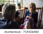 senior man taking wife photo... | Shutterstock . vector #715426483