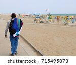 Small photo of poor walking salesman along the beach in summer