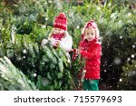 family selecting christmas tree.... | Shutterstock . vector #715579693