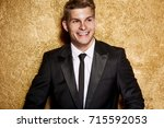 handsome man on gold background ... | Shutterstock . vector #715592053