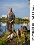 the guy stands on the lake ... | Shutterstock . vector #715654117