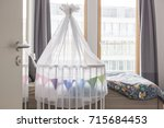 Small photo of Rollaway baby bed attached to parents bed in their bedroom, room sharing with a baby.