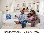 father sitting on sofa watching ... | Shutterstock . vector #715726957
