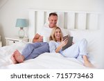 couple lying in bed looking at... | Shutterstock . vector #715773463