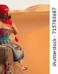 Small photo of Close up of Girl wearing colourful clothes, a head scarf and harem pants riding a camel across the Sahara Desert in Morocco, North Africa