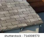 old gray asphalt shingle roof | Shutterstock . vector #716008573