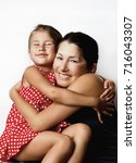 Small photo of Affectionate grandmother and her cute little granddaughter smile at the camera