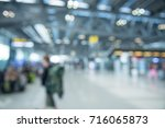 Small photo of Traveling concept. Travelers asian walking with a luggage at airport terminal and airport terminal blurred crowd of Travelling people on the Background.