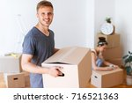 moving day. young man carrying... | Shutterstock . vector #716521363