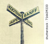 Small photo of Directional road signs. Signpost. Marker with yellow metal plates pointing direction to Canadian National Parks - Kootenay, Banff, Jasper, Yoho. Tourism and travel. Warm tone. Vintage style
