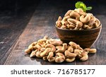 bowl with cashew nuts on wooden ... | Shutterstock . vector #716785177