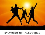 family in jumping at sunset... | Shutterstock .eps vector #716794813