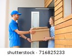 smiling delivery man in blue... | Shutterstock . vector #716825233