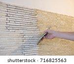 applying mosaic tiles on wall | Shutterstock . vector #716825563